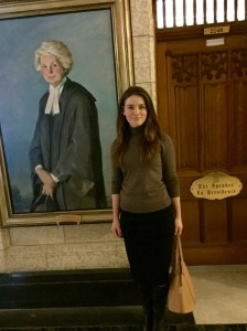 Yulia stands next to a portrait of the first female speaker of the Canadian House of Commons.